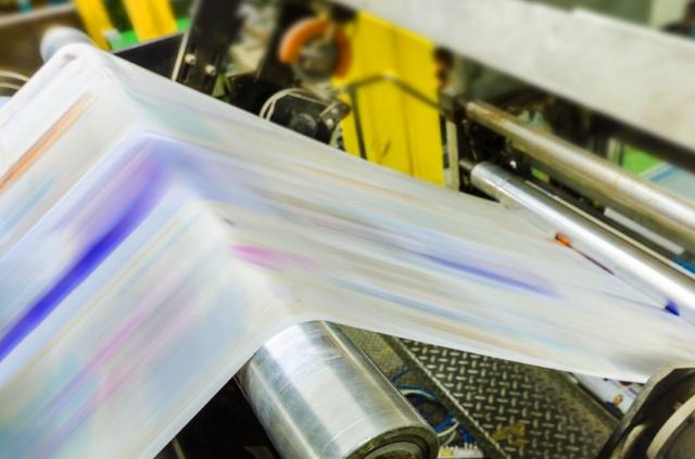 Foto van een drukppers. Dispersielak wordt tijdens het drukken aangebracht.