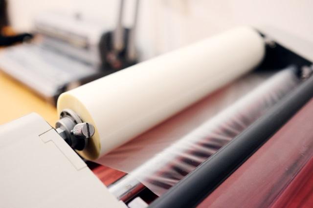 Op de foto is een machine te zien waarmee de beschermlaag laminaat wordt aangebracht.